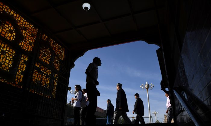 Uyghur men walking past the exit of an underpass after attending Eid al-Fitr prayers, marking the end of Ramadan, in Kashgar in China's northwest Xinjiang region on June 5, 2019. (Greg Baker/AFP/Getty Images)