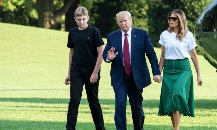 President Donald Trump (C), First Lady Melania Trump (R) and their son Barron Trump (L) return to the White House after two weeks spent at Trump's golf club in New Jersey on Aug. 18, 2019. (Eric Baradat/AFP/Getty Images)