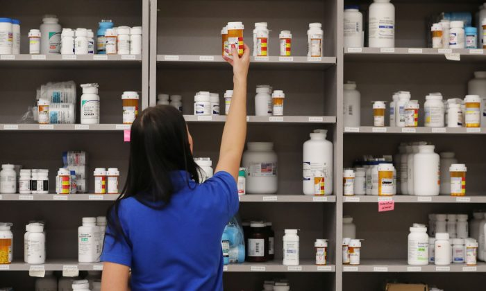A pharmacy technician grabs a bottle of drugs off a shelf at the central pharmacy of Intermountain Heathcare, in Midvale, Utah, on Sept. 10, 2018.  (George Frey/Getty Images)