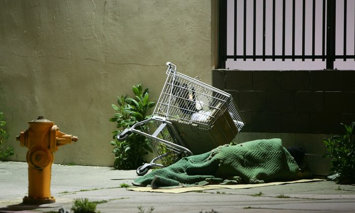 In this file image a homeless person sleeps by his shopping cart on a downtown sidewalk in the early morning hours in Los Angeles, California, on April 19, 2006. (David McNew/Getty Images)