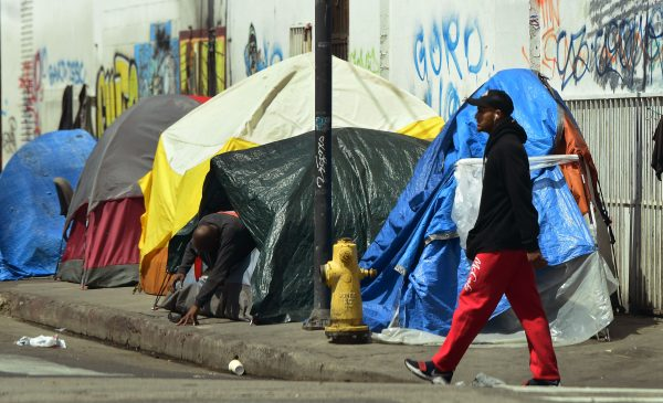 A homeless person walks by a tent
