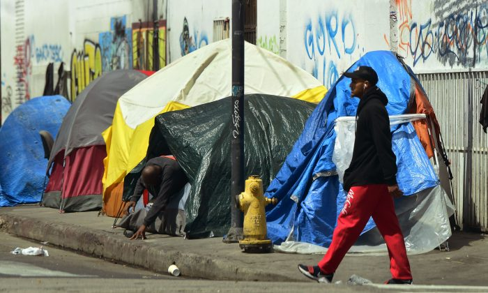 A person makes his way out of his tent among a row of tents along a sidewalk in downtown Los Angeles on May 30, 2019. (Frederic J. Brown/AFP/Getty Images)