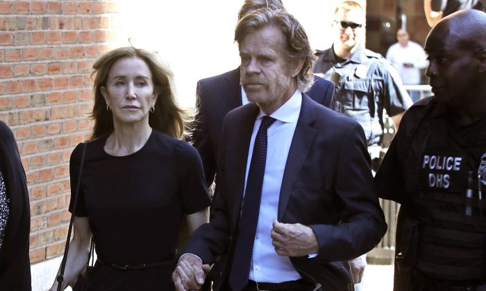 Felicity Huffman arrives at federal court with her husband William H. Macy for sentencing in a nationwide college admissions bribery scandal in Boston on Sept. 13, 2019. (AP Photo/Elise Amendola)