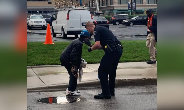 A police officer helps a man shave outside of Comerica Park in Detroit, Michigan, on Sept. 11, 2019. (Courtesy of Jill Metiva Schafer)