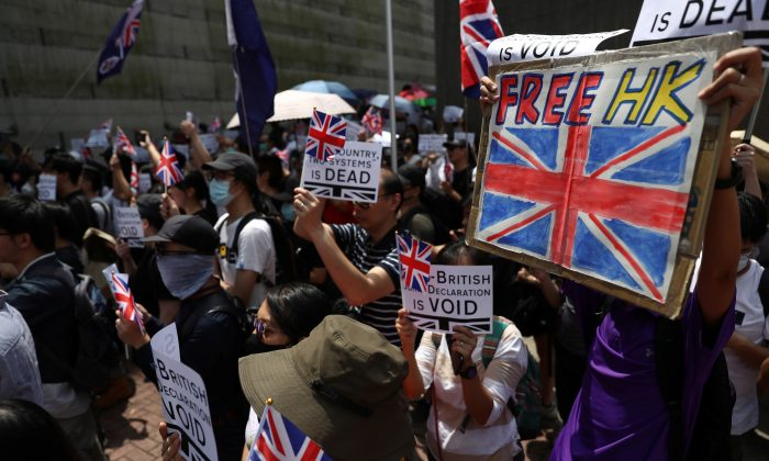 Protesters hold up banners, placards, Union Jack flags as they gather at the British consulate General in Hong Kong, China, to call on the UK to demand that China honors its commitments to the city's freedoms on Sept. 15, 2019. (Athit Perawongmetha/Reuters)