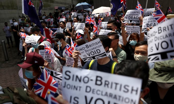 Protesters hold up banners, placards, Union Jack flags as they gather at the British consulate General in Hong Kong, China, on Sept. 15, 2019. (Athit Perawongmetha/Reuters)