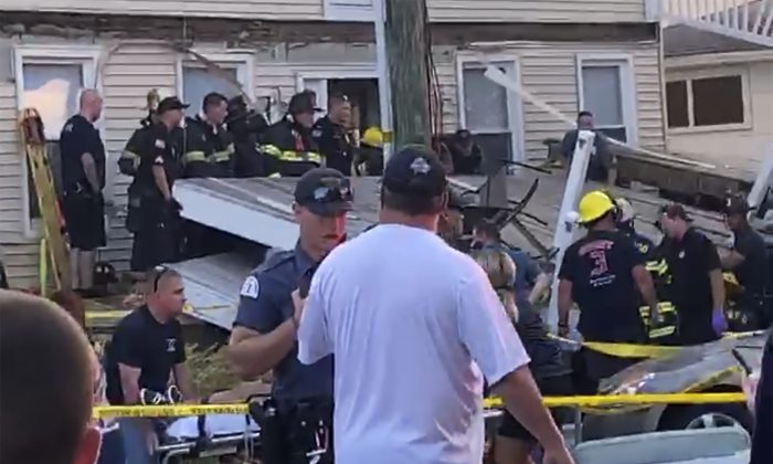 A first responder talks to an onlooker as others carry an injured person, while some others work the scene of a building structure damage, in the background, in Wildwood, N.J., on Sept. 14, 2019. (James Macheda via AP)