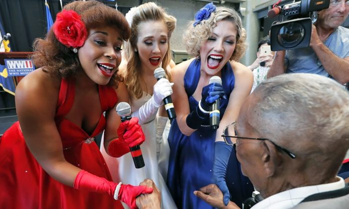 The Victory Belles singing trio sing happy birthday to veteran Lawrence Brooks (R) at the National World War II Museum in New Orleans, La., on Sept. 12, 2019. (AP Photo/Gerald Herbert)