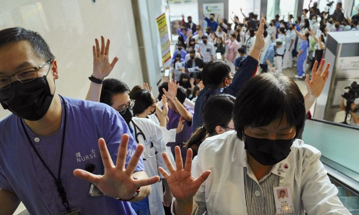 Medical workers display their palm with five fingers, signifying the five demands of protesters and chanted slogans as they stood in the foyer of the hospital before moving to different floors of the building at the Prince of Wales Hospital in Hong Kong on Sept. 16, 2019. (Vincent Yu/AP)