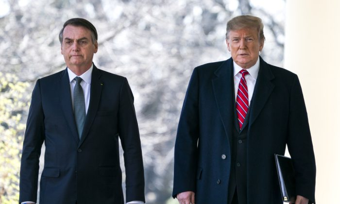U.S. President Donald Trump (R) and Brazilian President Jair Bolsonaro (L) walk down the Colonnade before a press conference at the Rose Garden of the White House in Washington, DC on March 19, 2019.
