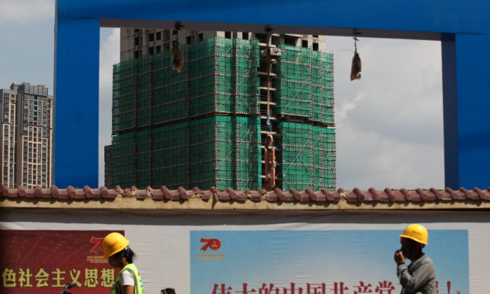 Workers walk past a construction site of residential buildings by property developer Country Garden in Kunming, Yunnan Province, China on Sept. 17, 2019. (Wong Campion/Reuters)