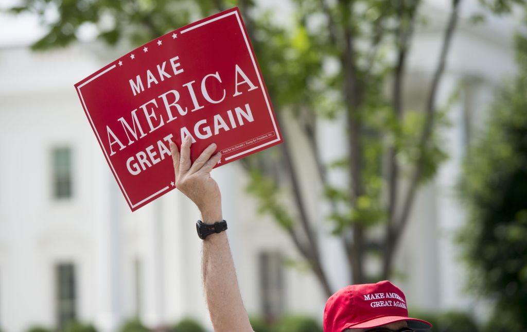 A man holds a Make America Great Again sign