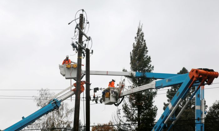 PG&E crew work on power lines to repair damage caused by the Camp Fire in Paradise, Calif., on Nov. 21, 2018. (Elijah Nouvelage/Reuters)