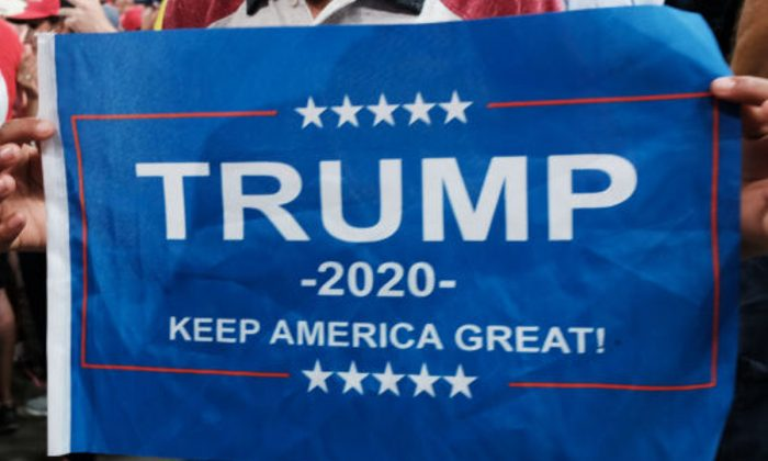 A Donald Trump supporter holds a Keep America Great banner at a rally in Manchester, New Hampshire, on Aug. 15, 2019. (Spencer Platt/Getty Images)