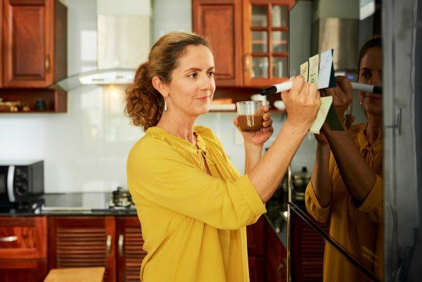 Woman writing shopping list on fridge