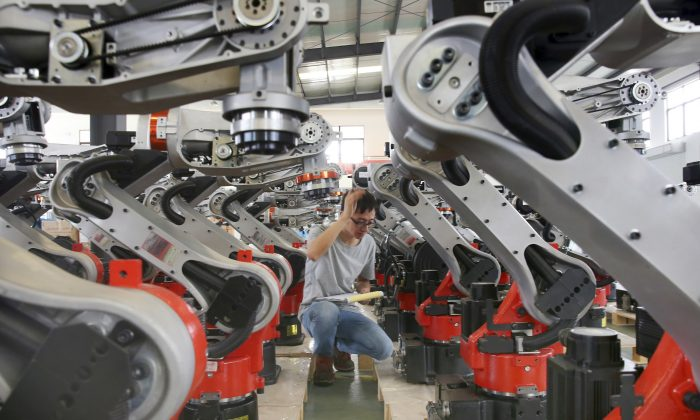 A worker checks on the robotic arms at a factory making industrial robots in Zhengyu town of Haimen City, Jiangsu Province, China on Sept. 11, 2019. (Chinatopix via AP)