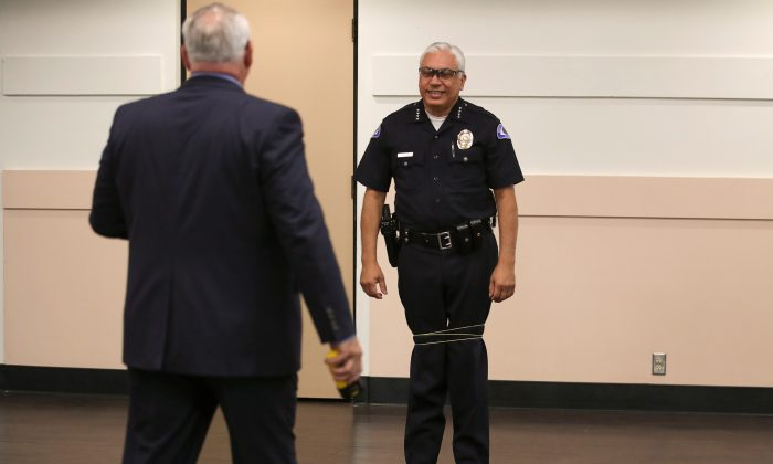 The city of Bell's chief of police Carlos Islas reacts after Wrap Technologies CEO Michael Rothans tests on him a new non-lethal weapon that discharges an 8 foot bola style Kevlar tether at 640 feet per second to entangle a subject, in Bell Police Department, California, Sept. 5, 2019. (Mike Blake/Reuters)