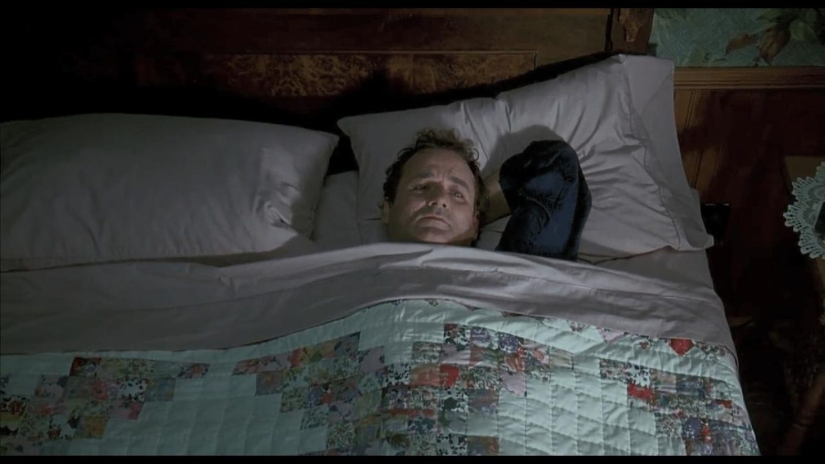 a man in bed with quilt