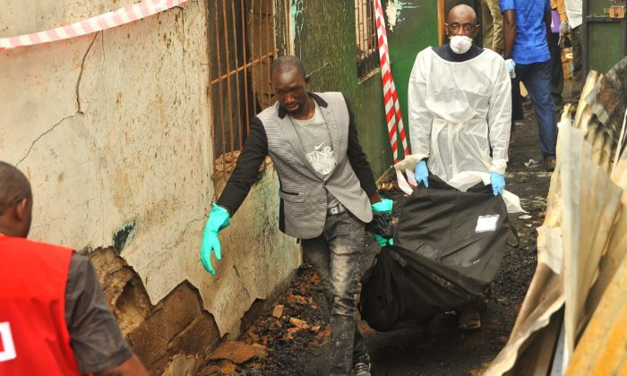 Rescuers hold a body after a fire at a Koranic school that killed at least 27 children and two teachers in Monrovia, Liberia, on Sept. 18, 2019. (ZOOM DOSSO/AFP/Getty Images)