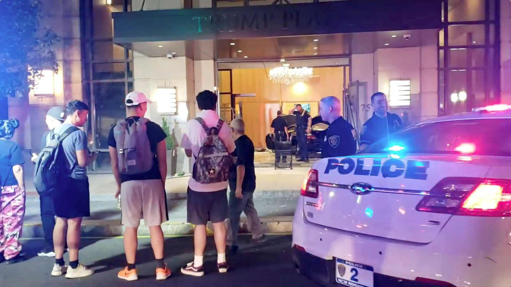 People and police officers stand outside Trump Plaza after a car crashed into the building's lobby in New Rochelle, New York