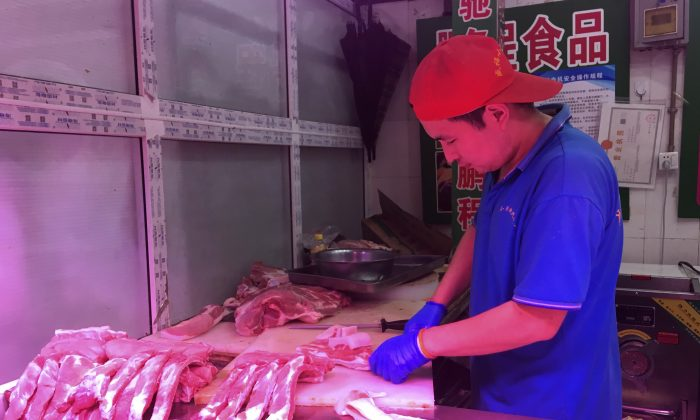 A butcher slices cuts of pork at a meat market in Beijing on Sept. 11, 2019. (Fu Ting/AP)