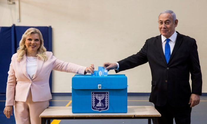 Israeli Prime Minister Benjamin Netanyahu and his wife Sara casts their votes during Israel's parliamentary election at a polling station in Jerusalem Sept. 17, 2019. (Heidi Levine/Pool via REUTERS)