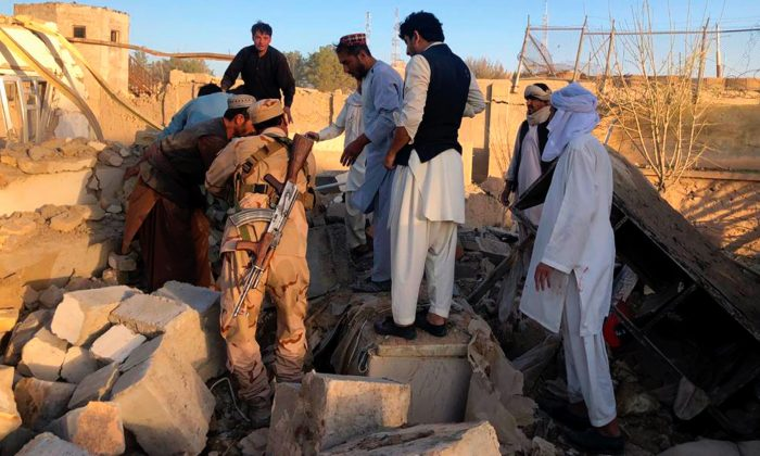 Afghan security members and people work at the site of a suicide attack in Zabul, Afghanistan, on Sept. 19, 2019. (Ahmad Wali Sarhadi/AP Photo)