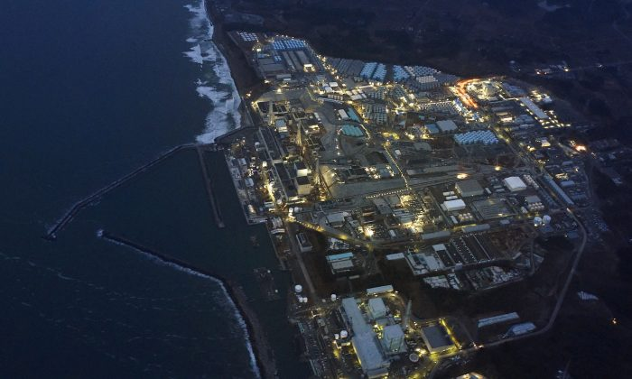 Tokyo Electric Power Co.'s (TEPCO) tsunami-crippled Fukushima Daiichi nuclear power plant is illuminated for decommissioning operation in the dusk in Okuma town, Fukushima prefecture, Japan, in this aerial view photo taken by Kyodo on March 10, 2016. (Kyodo/File Photo via Reuters)