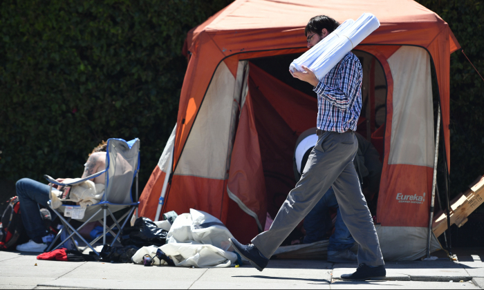 A man carrying blueprints passes a homeless encampment in downtown San Francisco, Calif., on June, 27, 2016. (Josh Edelson/AFP/Getty Images)