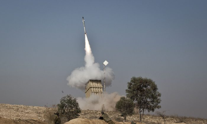 An Israeli soldier lies on the ground as missiles are fired from an Iron Dome anti-missile station near the city of Beer Sheva, Israel on Nov. 15, 2012. (Ilia Yefimovich/Getty Images)