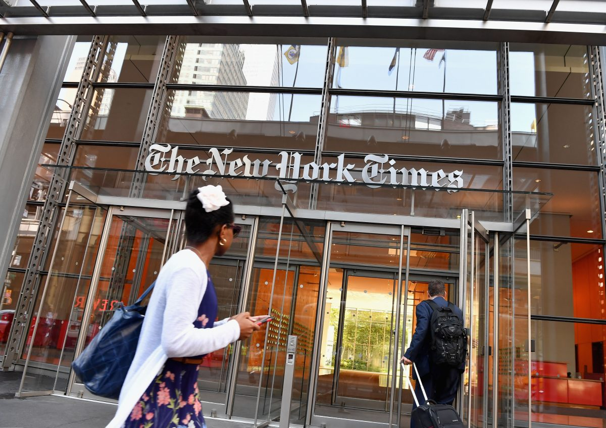 People walk by the front of the New York Times