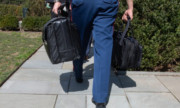 """A military aide to President Donald Trump carries a briefcase known as the """"nuclear football"""" through the Rose Garden of the White House on March 14, 2019. (Saul Loeb/AFP/Getty Images)"""