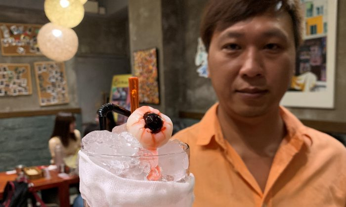 "Spicy Andong owner Roy Ma poses with a glass of ""eye for an eye,"" a blackcurrant longan soda with strawberry syrup, at his restaurant in Hong Kong, China on Sept. 19, 2019. (Vorasit Satienlerk/Reuters)"