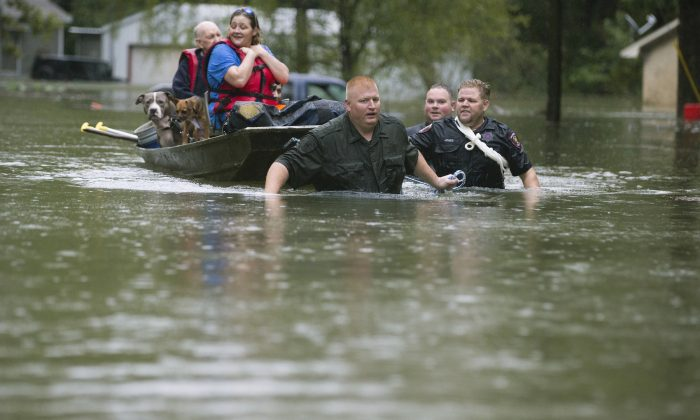Splendora Police Lt. Troy Teller, left, Cpl. Jacob Rutherford, and Mike Jones pull a boat carrying Anita McFadden and Fred Stewart from their flooded neighborhood inundated by rain from Tropical Depression Imelda in Spendora, Texas, on Sept. 19, 2019. (Brett Coomer/Houston Chronicle via AP)