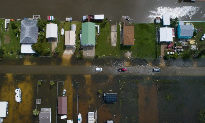 Cars drive on a flooded street in Sargent, Texas, as seen in this aerial photo Wednesday, Sept. 18, 2019.(Mark Mulligan/Houston Chronicle via AP)