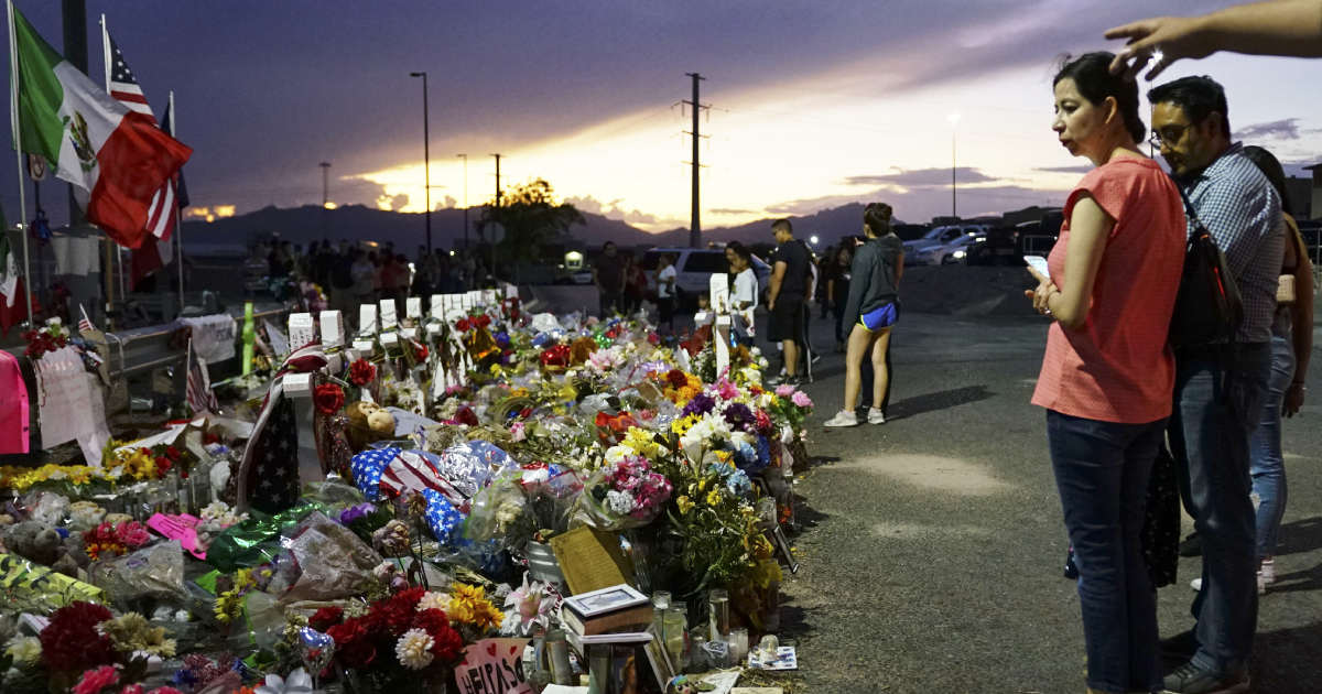 People gather at a makeshift memorial