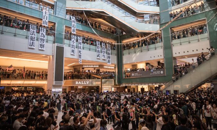 "Hong Kong pro-democracy protesters sing songs and chant slogans during a rally inside a shopping mall in Sha Tin on Sept. 22, 2019. Pro-democracy protesters have continued demonstrations across Hong Kong, calling for the city's Chief Executive Carrie Lam to immediately meet the rest of their demands, including an independent inquiry into police brutality, the retraction of the word ""riot"" to describe the rallies, and genuine universal suffrage, as the territory faces a leadership crisis. (Chris McGrath/Getty Images)"