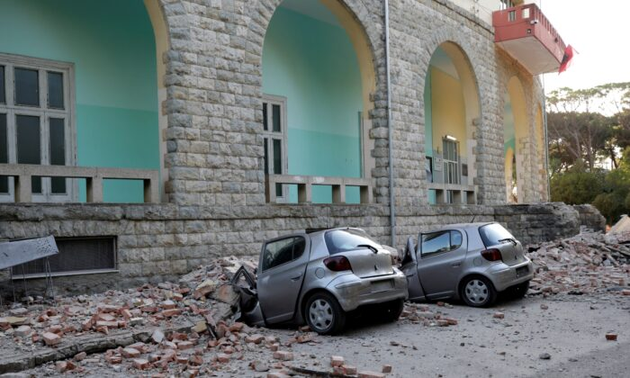 Destroyed cars stand next to a damaged building after an earthquake in Tirana, Albania, on Sept. 21, 2019. (Florion Goga/Reuters)