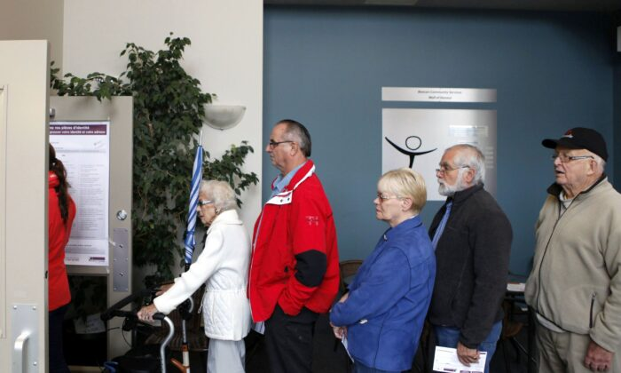 People wait in line to cast their ballots in Sidney, B.C., in Canada's last federal election on Oct. 19, 2015. (The Canadian Press/Chad Hipolit)