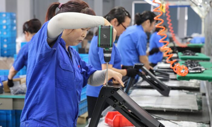 Workers produce desks for export to the United States, France, Germany, and other countries, at a factory in Nantong in China's eastern Jiangsu Province on Sept. 4, 2019. (STR/AFP/Getty Images)
