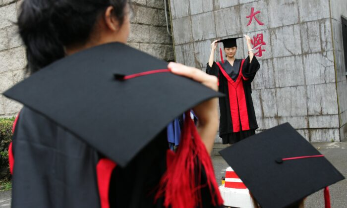 Graduates pose for pictures during a graduation ceremony at Renmin University in Beijing on June 29, 2006. Chinese investor Zhang Lei has donated millions to Renmin University to establish an artificial intelligence research institute. (China Photos/Getty Images)
