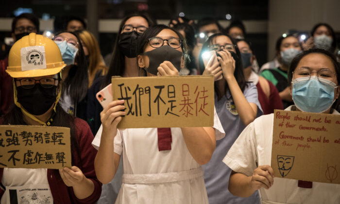 Secondary school students sing songs and chant slogans during a sing-along protest inside a shopping mall in Hong Kong on Sept. 23, 2019. (Chris McGrath/Getty Images)