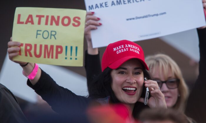 A woman holds a sign expressing Latino support for then-Republican presidential candidate Donald Trump at his campaign rally at the Orange County Fair and Event Center, April 28, 2016, in Costa Mesa, California. (DAVID MCNEW/AFP/Getty Images)