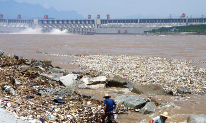 Two workers clean up trash along the bank of the Yangtze River near the Three Gorges Dam in Yichang, in central China's Hubei Province on Aug. 1, 2010. Layers of trash floating in the Yangtze River were threatening to jam China's massive Three Gorges hydroelectric dam, state media reported on Aug. 2. (China Out/STR/AFP/Getty Images)