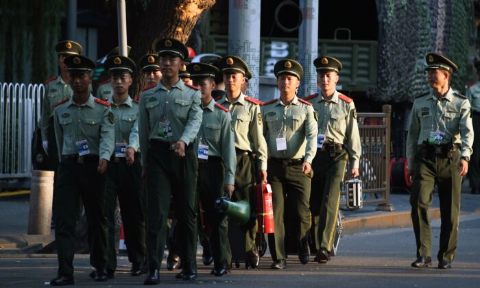 Chinese paramilitary police walk in a street next to Tiananmen Square ahead of an overnight rehearsal of a military parade to mark Communist China's 70th anniversary, in Beijing, China, on Sept. 7, 2019. (Greg Baker/AFP/Getty Images)