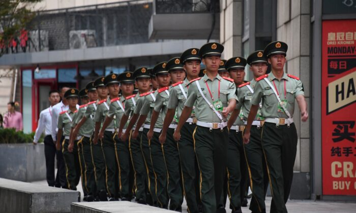 Paramilitary policemen march behind a mall next to the Worker's Stadium, ahead of an overnight rehearsal of a military parade in Beijing on Sept. 14, 2019. Much of the center of Beijing has been closed off for the rehearsal of the Oct. 1 parade, which will mark the 70th anniversary of the founding of the People's Republic of China. (Greg Baker/AFP/Getty Images)