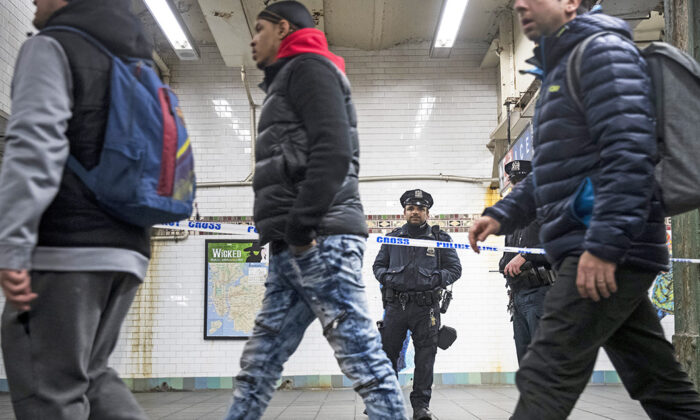 Commuters exit a train as a police officer stands in a cordoned off subway station walkway in New York, on Dec. 11, 2017. (Drew Angerer/Getty Images)
