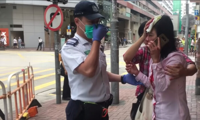 Liao Qiulan speaks with a police officer after being attacked by a man with a rod in Hong Kong on Sept. 24, 2019. (The Epoch Times)