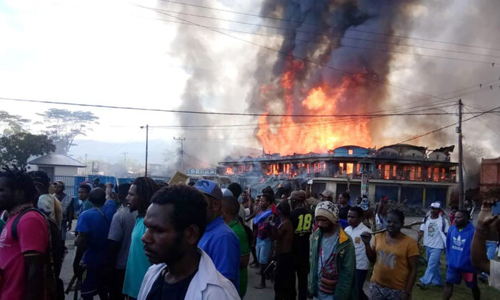 People gather as shops burn in the background during a protest in Wamena in Papua province, Indonesia, Monday, Sept 23, 2019. (AP Photo)