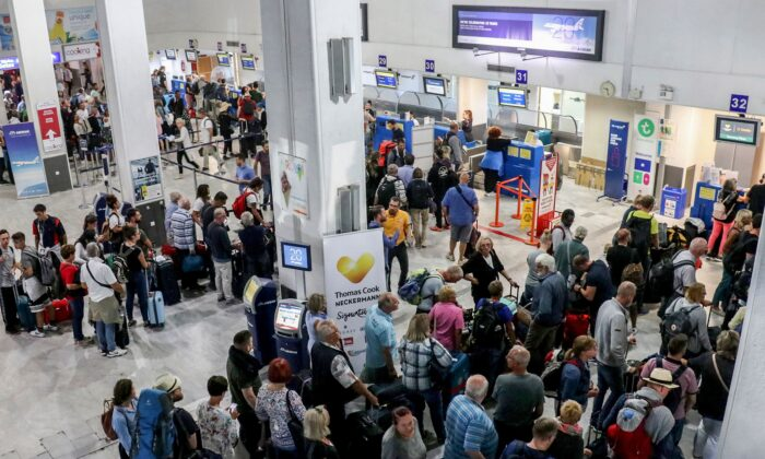 Tourists wait at a Thomas Cook company counter at Heraklion airport on the island of Crete on Sept. 23, 2019. (Costas Metaxakis/AFP/Getty Images)